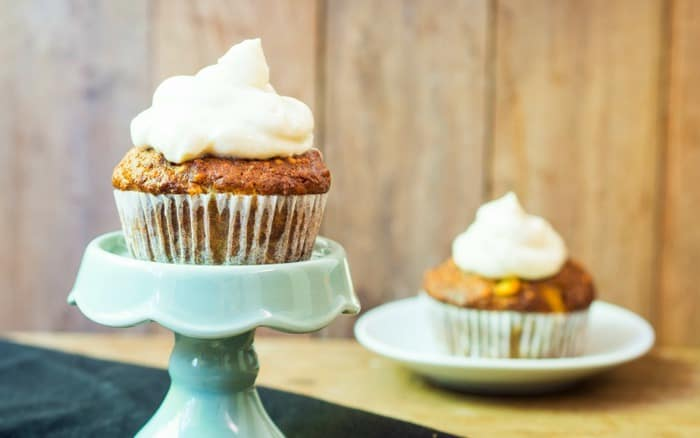 A photo of a carrot cake muffins, one on a cake stand and one in the background