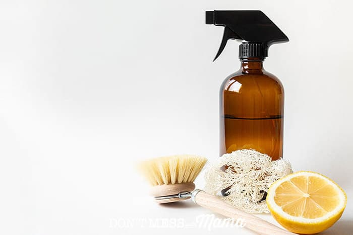 Closeup of glass spray bottle cleaner next to a scrub brush and lemon