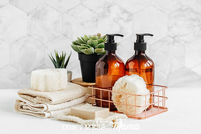 Closeup of bubble bath bottles with towels and soap on a table