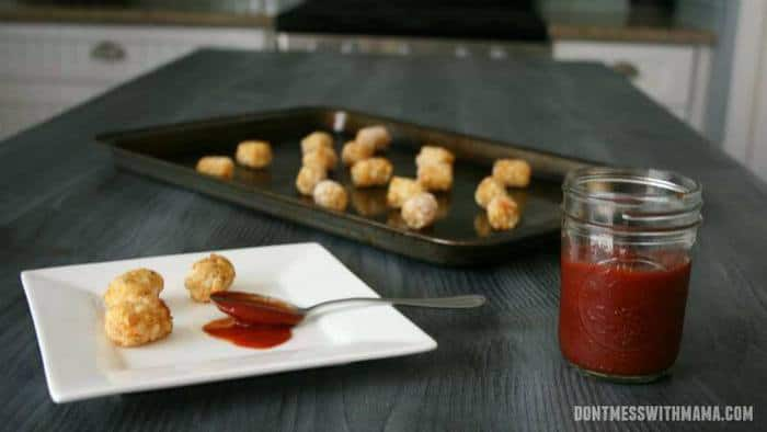 A mason jar filled with homemade ketchup on a counter top with tater tots