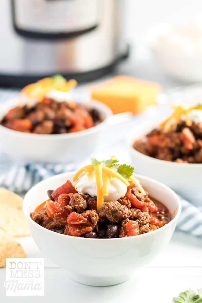 Closeup of beef chili in a bowl with an Instant Pot and cheese in the background