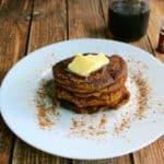Einkorn Buttermilk Pumpkin Pancakes on a white plate dusted with cinnamon and topped with butter