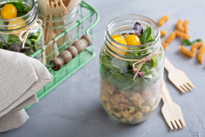 two salads in mason jars sitting on a blue work surface