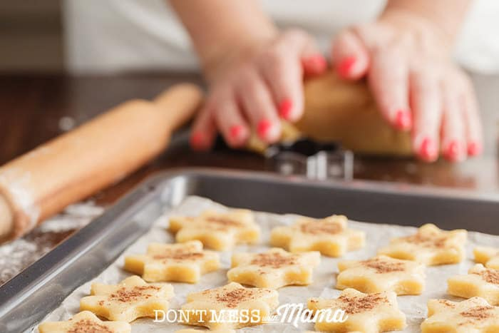 Closeup of hands rolling cookie dough and cookies on a baking sheet