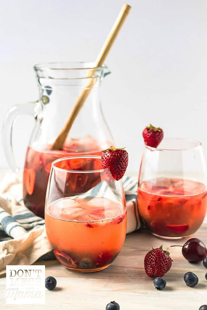 White sangria in glasses with a pitcher in the background