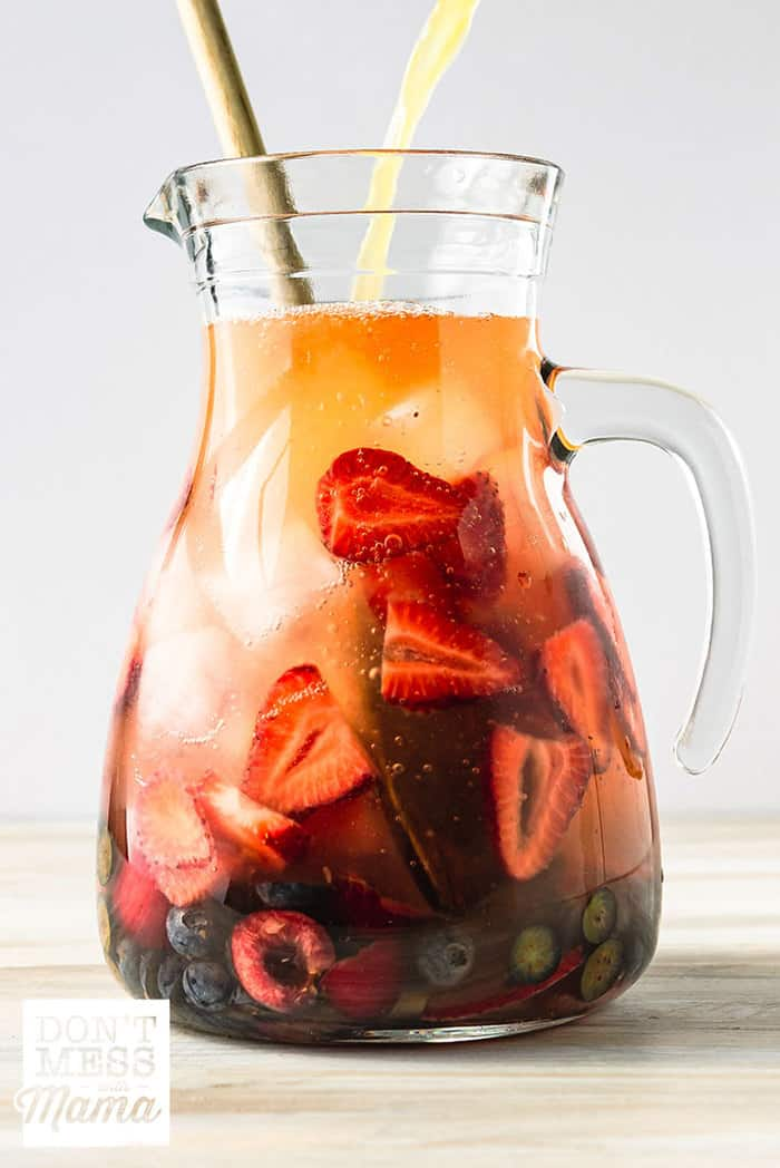 White sangria in a glass pitcher with fresh fruit