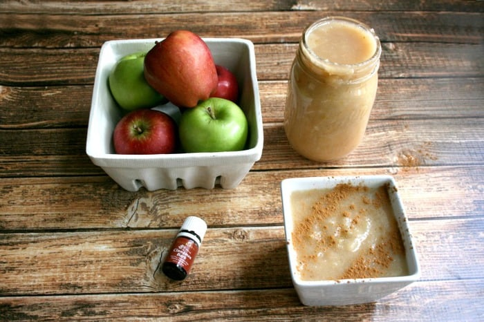 A photo of instant pot applesauce in a glass jar and white ramekin with a bowl of apples at the side