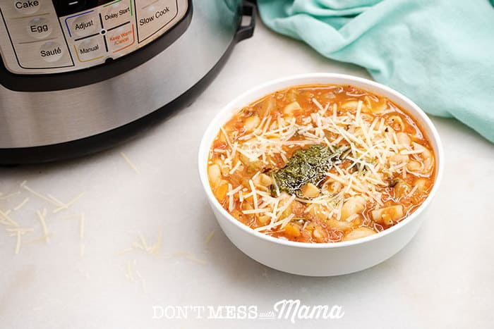 Closeup of minestrone soup in a bowl with an Instant Pot in the background