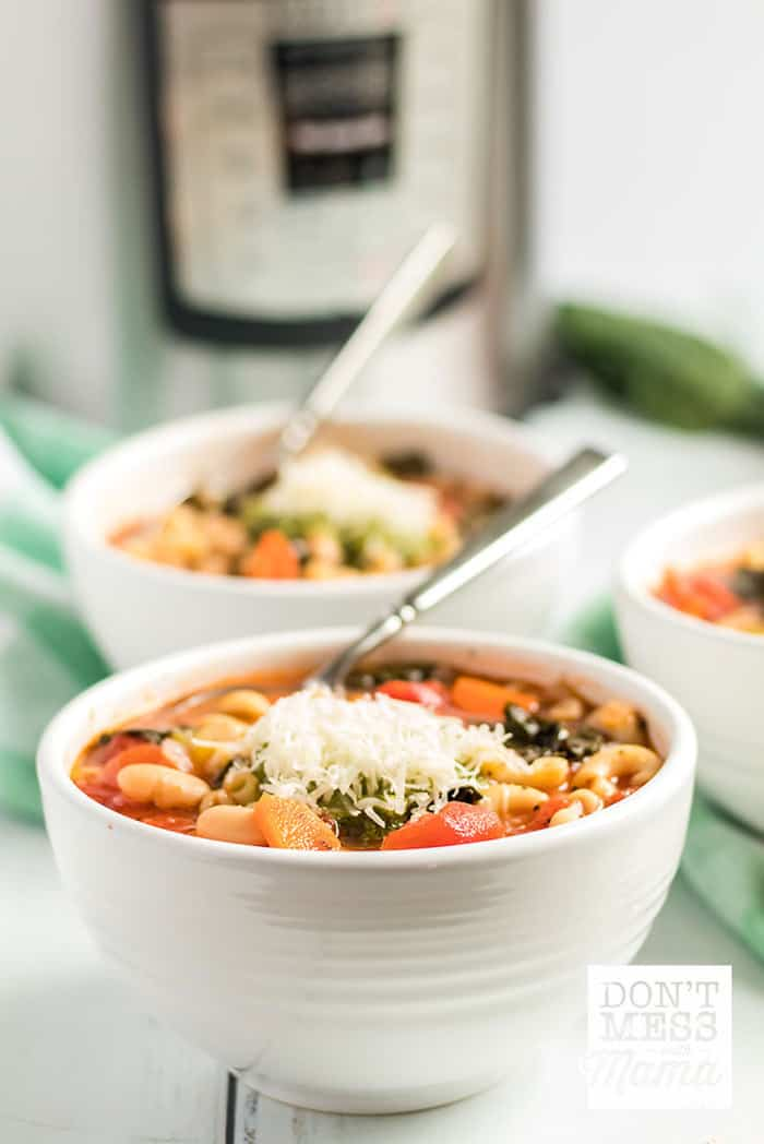 Instant Pot Minestrone soup in two white bowls topped with Parmesan cheese