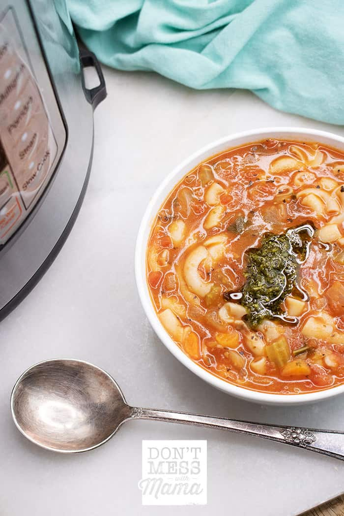 Closeup of minestrone soup with an Instant Pot pressure cooker in the background