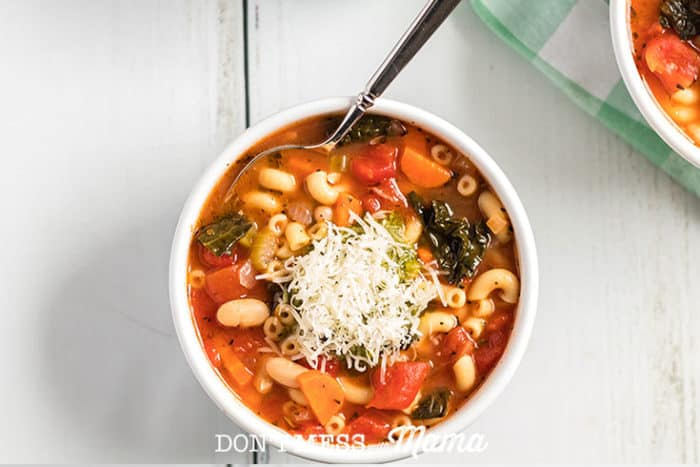 Instant Pot Minestrone soup in a white bowl topped with Parmesan cheese