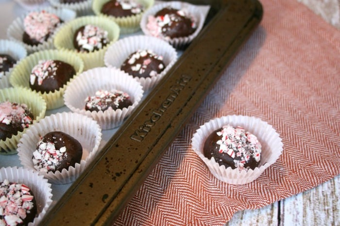 A close up of avocado truffles in little cases topped with sprinkles