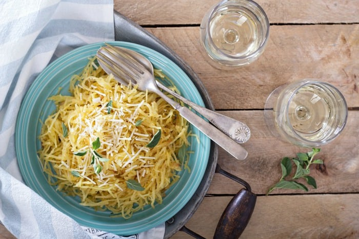 Spaghetti Squash pasta Aglio E Olio in a blue bowl on a wooden surface