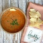 A bowl of slow cooker chicken tortilla soup next to tortilla chips