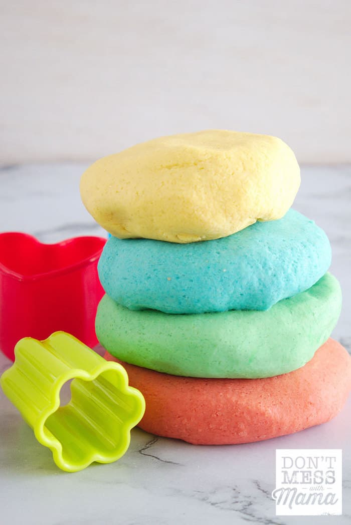Stacked DIY Play Dough on a table with cookie cutters