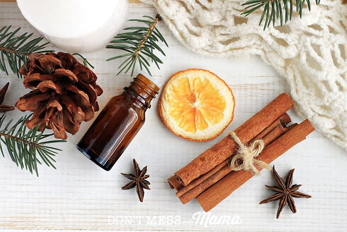 A bottle of essential oils and a cinnamon stick, slice or orange and spices on a wooden surface
