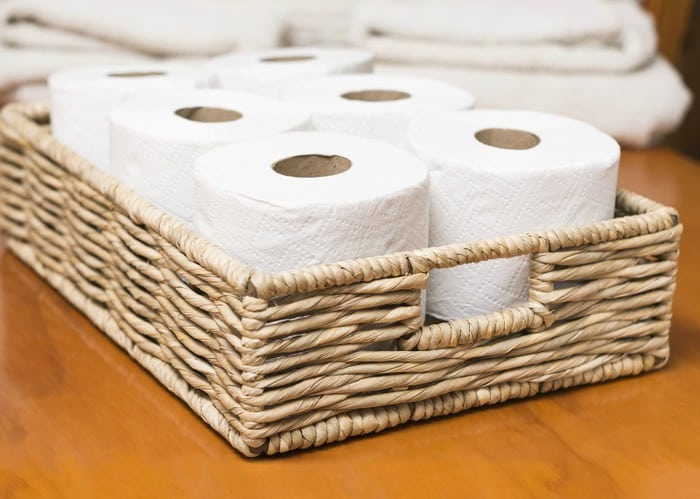 A photo of toilet rolls in a wicker basket
