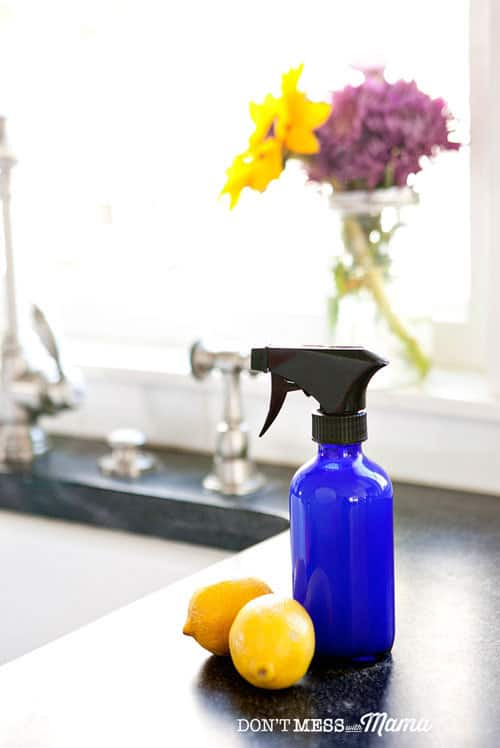 Closeup of blue spray bottle of natural disinfectant with lemons and flowers in background