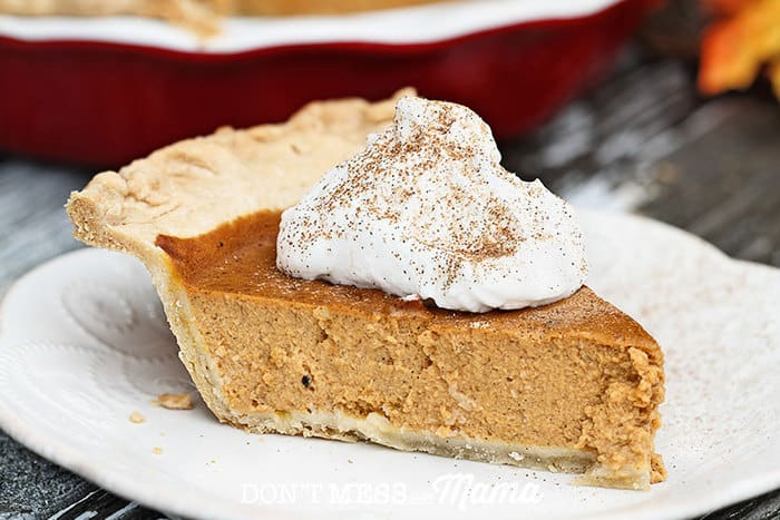 Closeup of a slice of pumpkin pie on a plate with whipped cream
