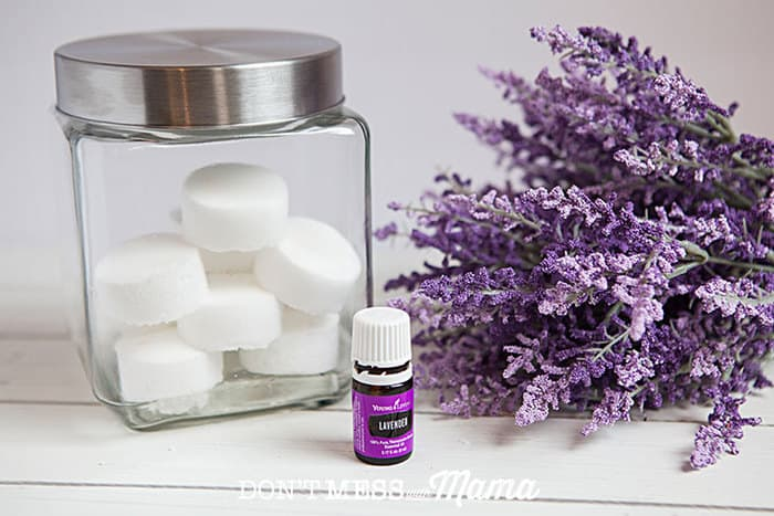 Closeup of glass jar with shower melts inside next to a bottle of lavender essential oil and fresh lavender flowers