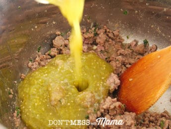 pouring salsa verde onto cooked ground beef
