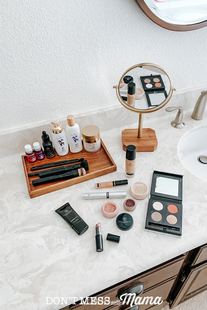 Savvy Minerals lipstick, foundation powder, makeup brushes on a bathroom counter in a pretty bathroom