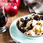 Instant Pot Oatmeal in a blue bowl topped with raisins and apples