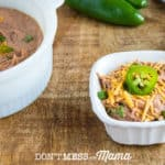 Instant Pot Refried Beans in a white dish topped with cheese