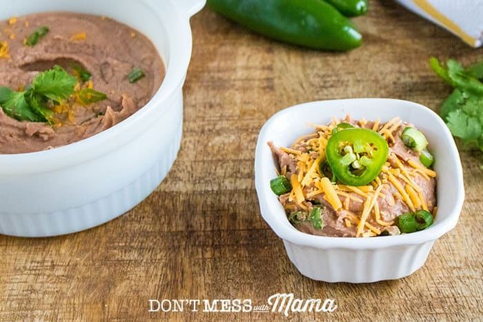 Instant Pot Refried Beans in a small bowl topped with grated cheese