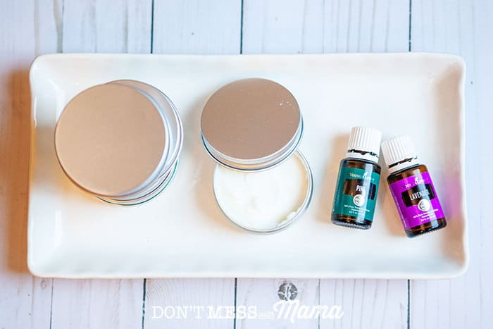 White plate with beard balm in a tin and bottles of pine and lavender essential oils
