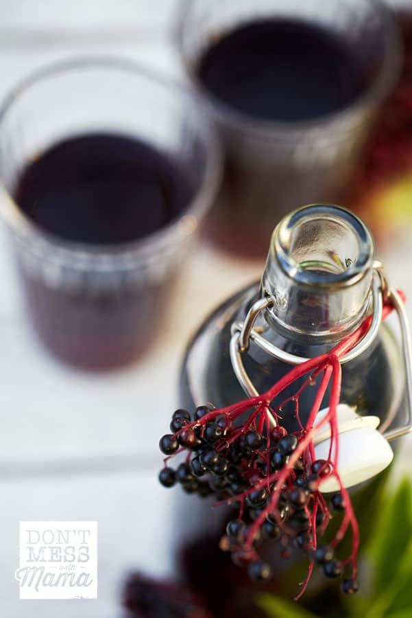 Closeup of elderberries and bottle of elderberry syrup