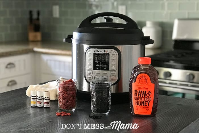 Closeup of Instant Pot with dried elderberries and honey on a table