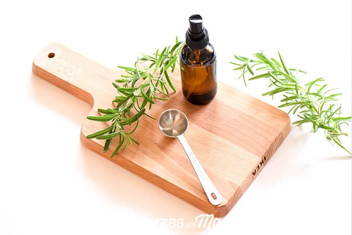 Closeup of DIY dry shampoo spray bottle on a cutting board with rosemary in the background
