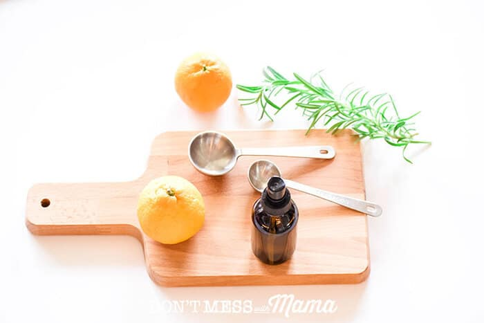 Closeup of DIY dry shampoo spray with oranges and rosemary on a cutting board