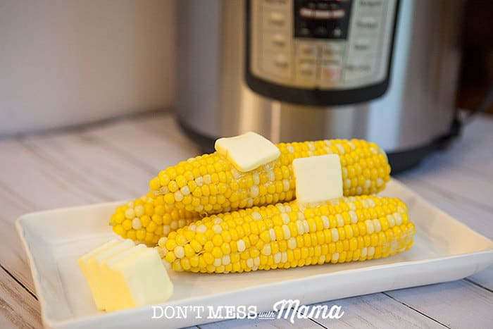 Corn on the Cob on a plate in front of an instant pot