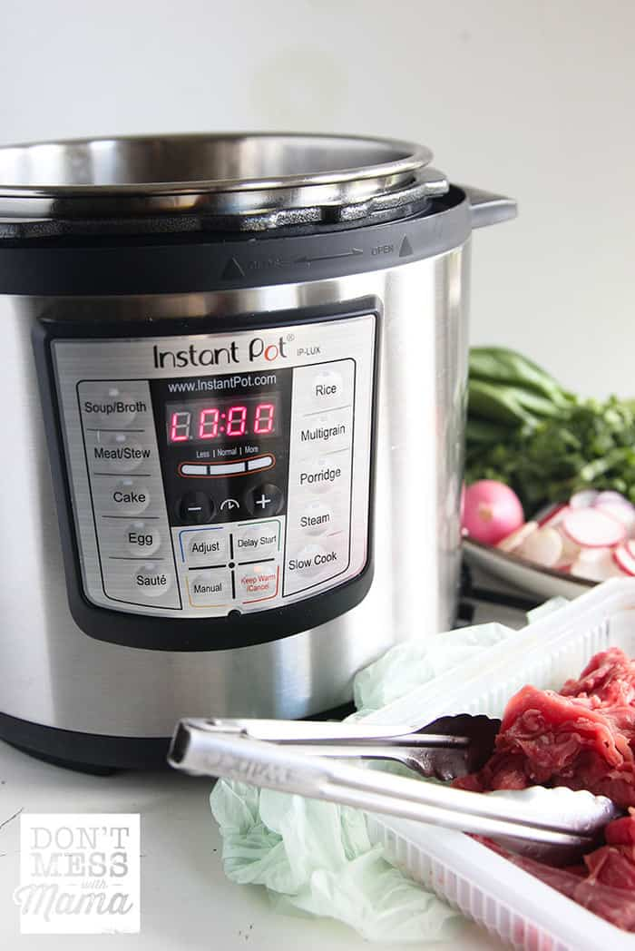 Closeup of Instant Pot with Vietnamese pho ingredients in the background