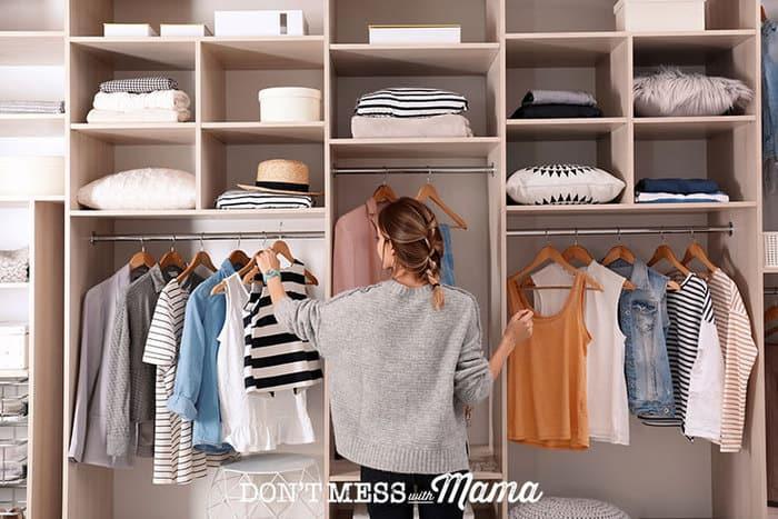 Woman arranging clothes in a closet