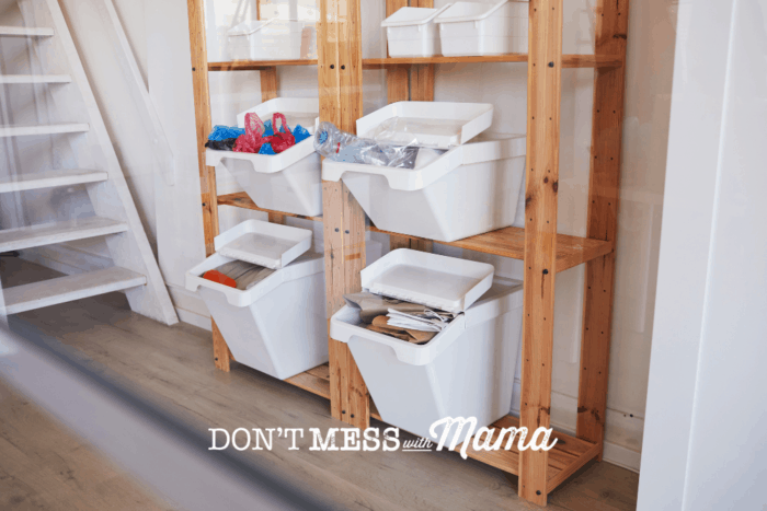 white bins on shelves with recycling organized