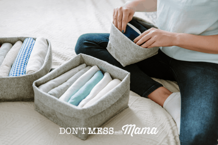 woman organizing clothing into baskets