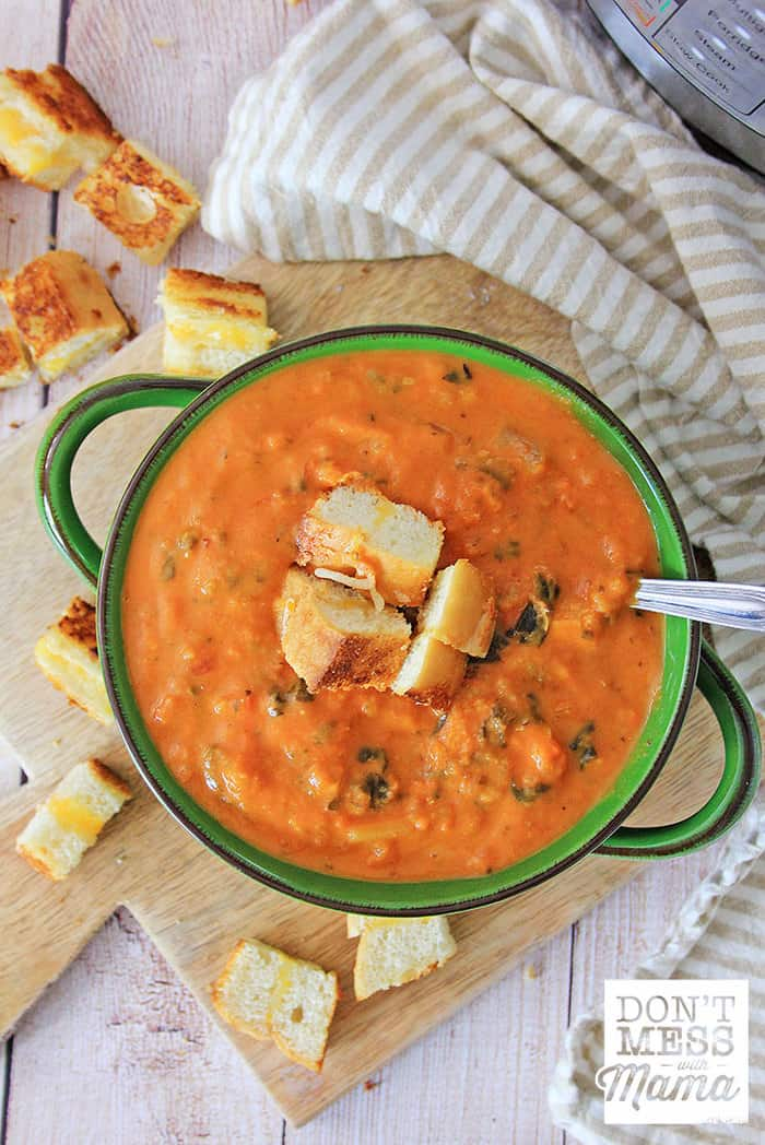 Overview look at creamy tomato soup in a green bowl topped with grilled cheese croutons