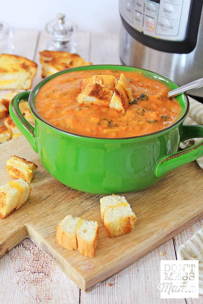Closeup of creamy tomato soup with grilled cheese croutons next to an Instant Pot pressure cooker