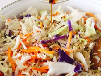 adding gluten-free soy sauce to a pot with shredded cabbage and ground chicken