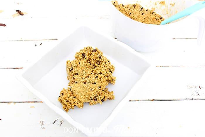pouring granola mixture into a 9x9 baking pan