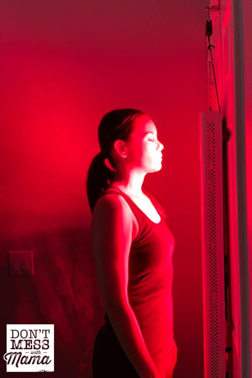 woman standing in front of a red light therapy unit