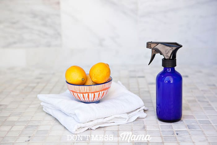 blue glass spray bottle in a shower next to a towel and bowl of lemons