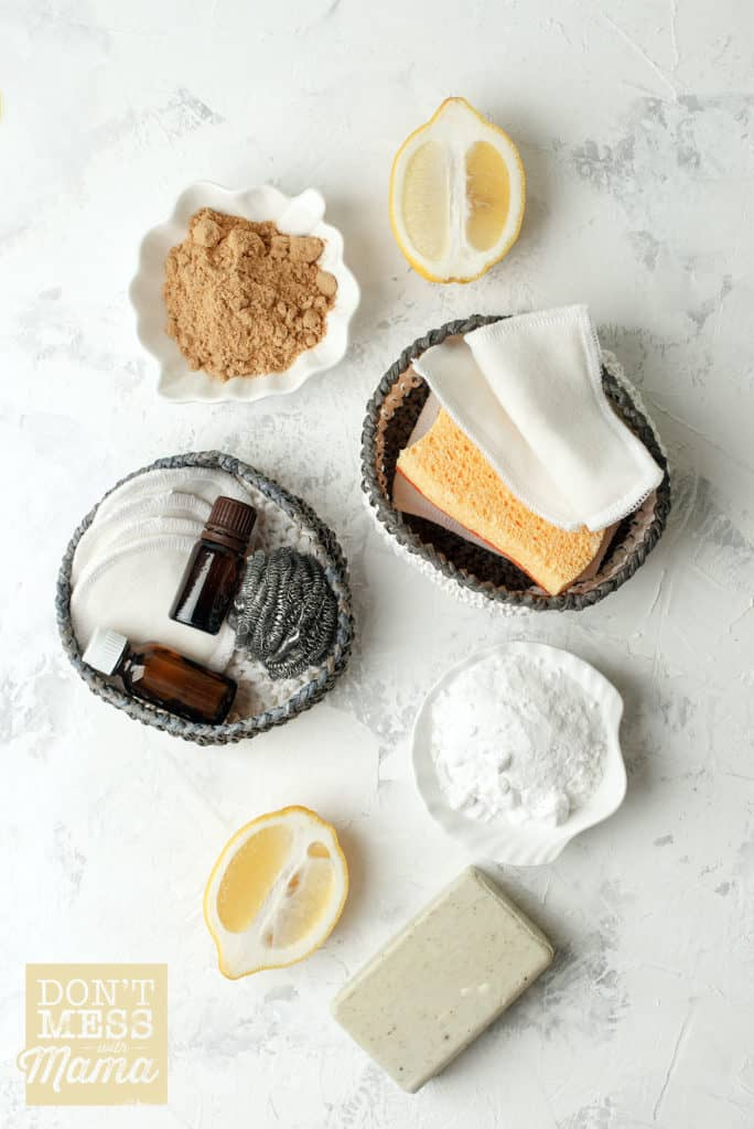 natural cleaning supplies like lemon, baking soda, sponges and essential oils on a table