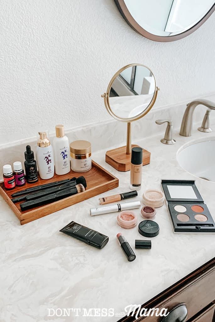 Savvy Minerals makeup liquid foundation bottles, makeup primer bottle mascara, and foundation powder on a bathroom counter