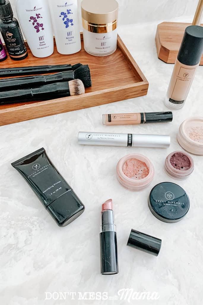 Savvy Minerals magnifying primer, lipstick, eye shadow, mascara, and foundation powder on a bathroom counter