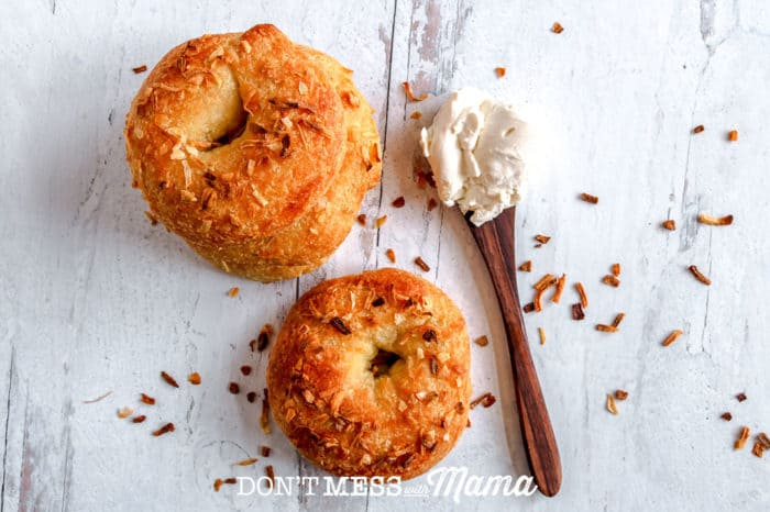 two onion bagels with spoon of cream cheese