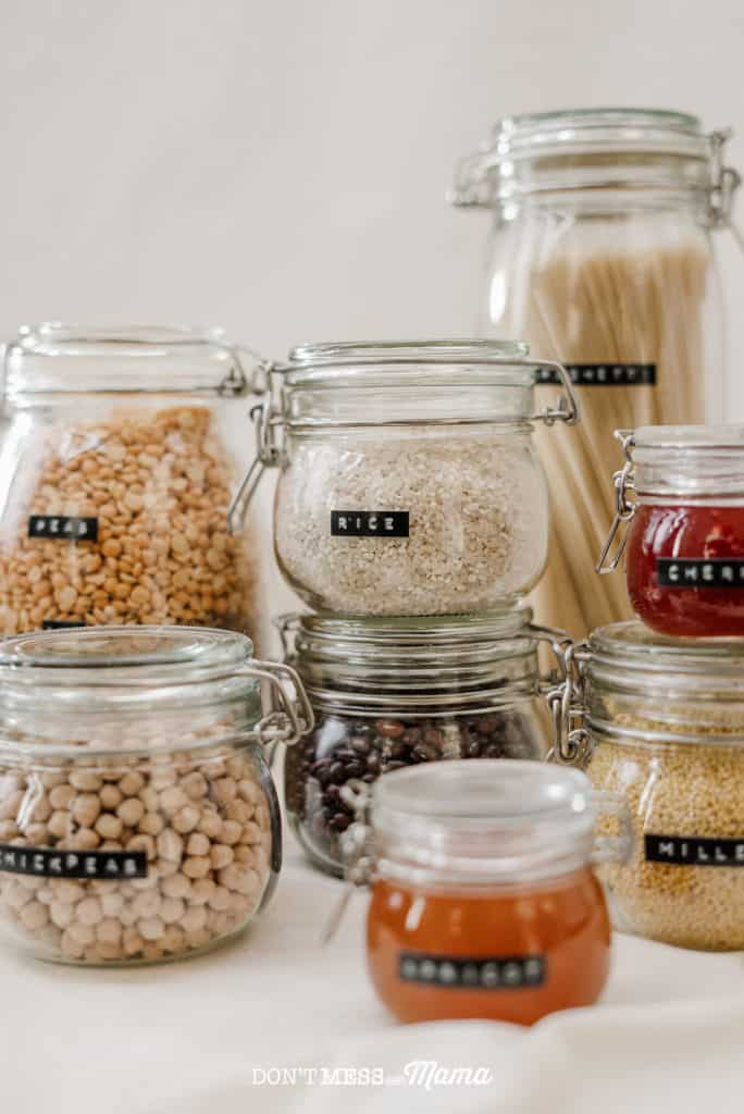 glass jars filled with dry food like beans, rice stacked in a pantry